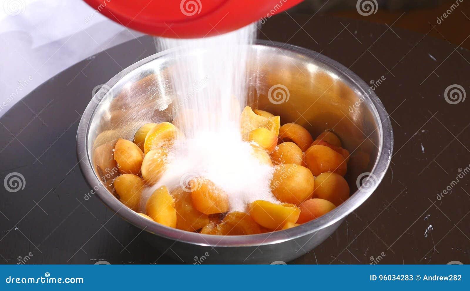 Cukier spada na talerzu morele na drewno stole z bliska
