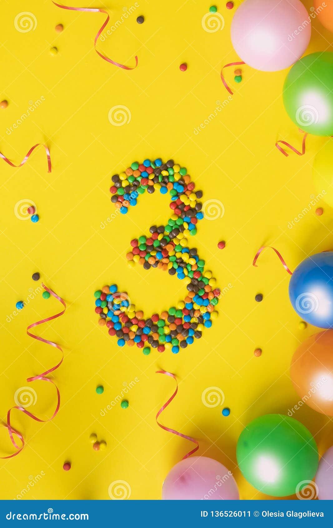 Cukierki liczą 3 z kolorowymi balonami na żółtym tle Pojęcie dla urodzin