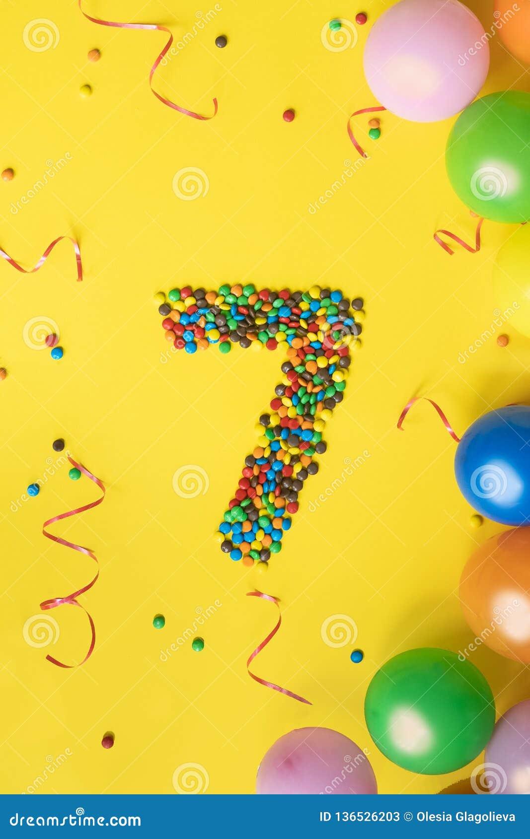 Cukierki liczą 7 z kolorowymi balonami na żółtym tle Pojęcie dla urodzin