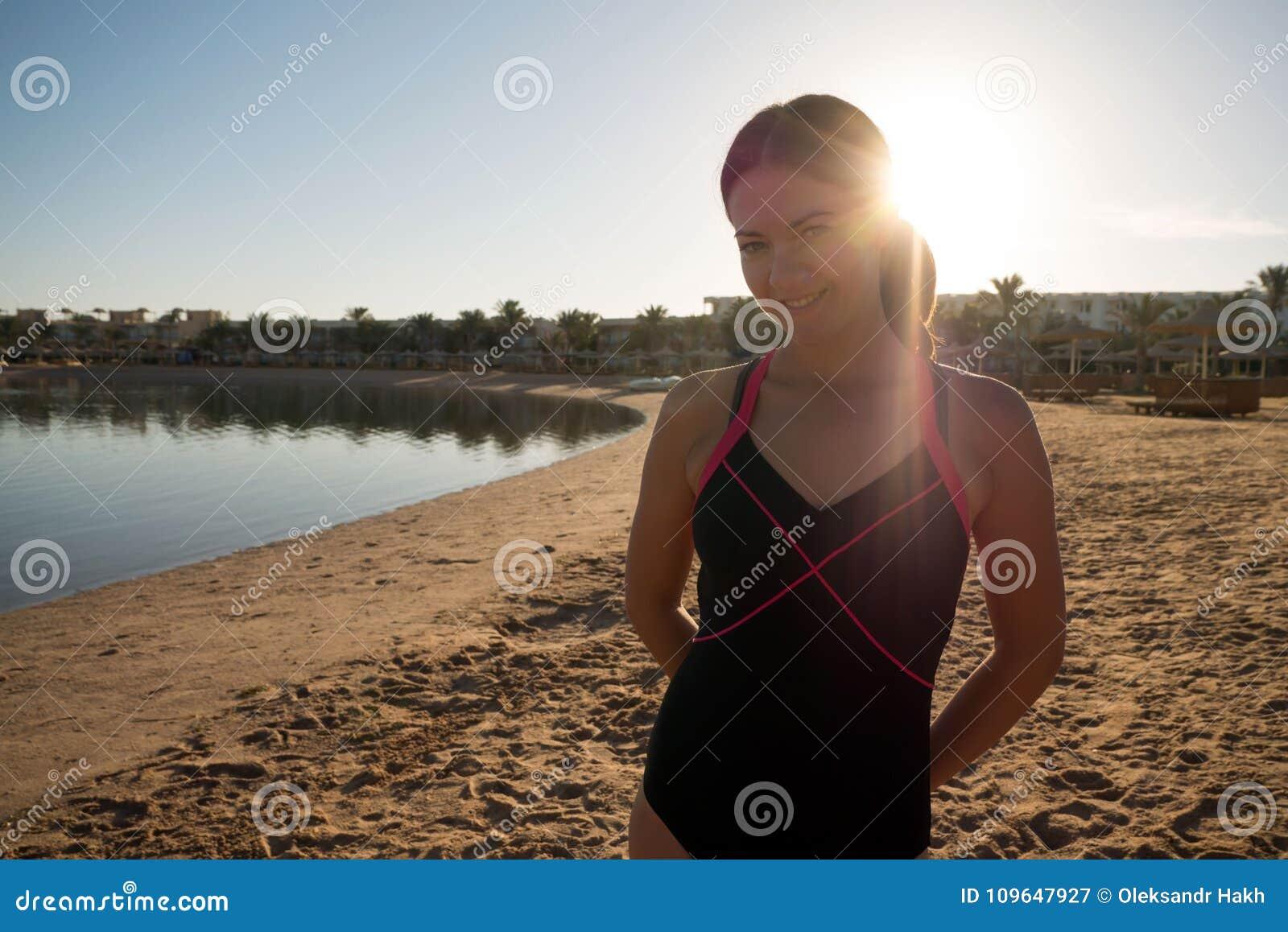 Cukierki, nikli dziewczyna stojaki na plaży przeciw zmierzchowi Promienie słońce błyszczą w kamerze