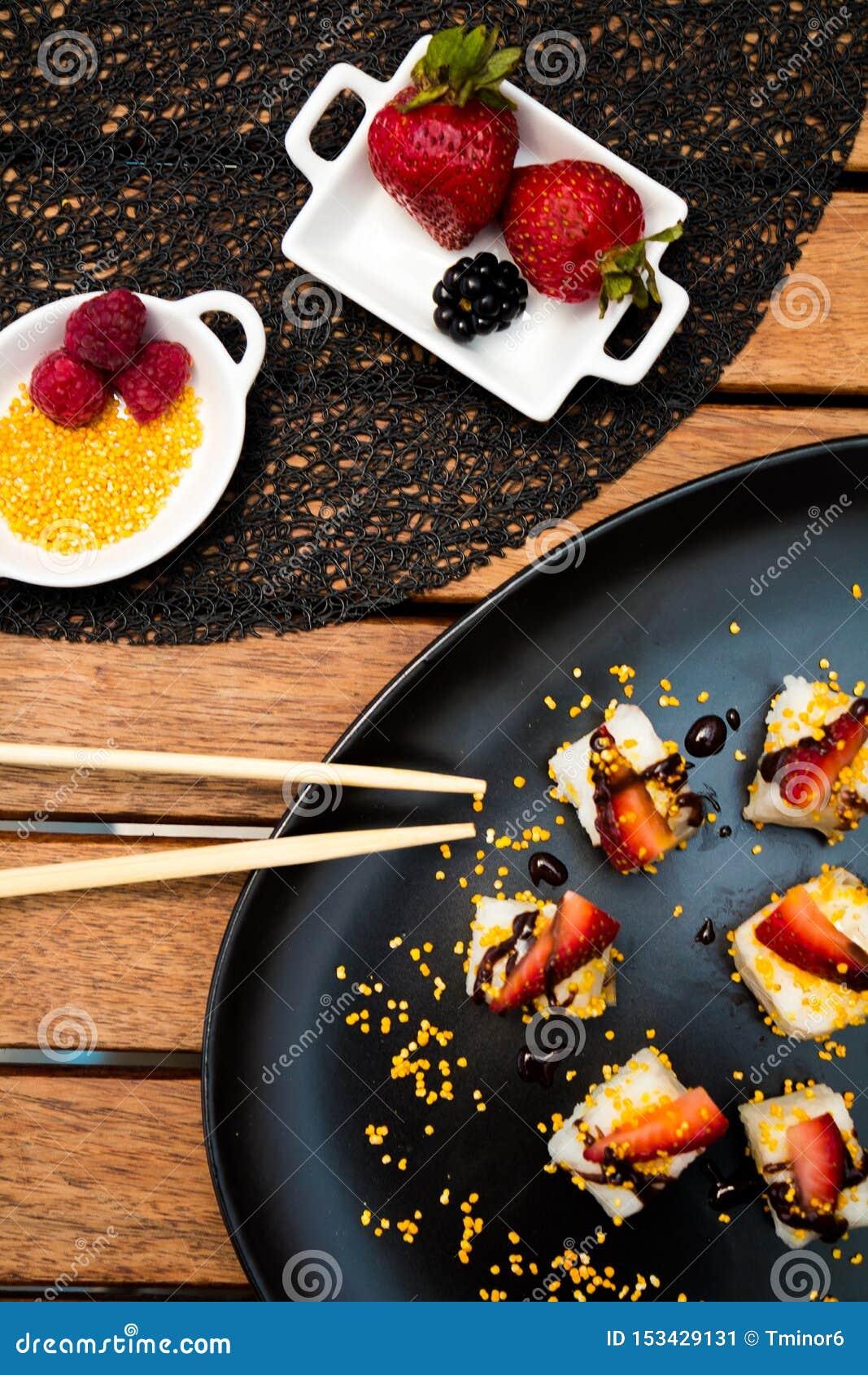 A culinária japonesa serviu em placas com bagas e sementes na tabela de madeira