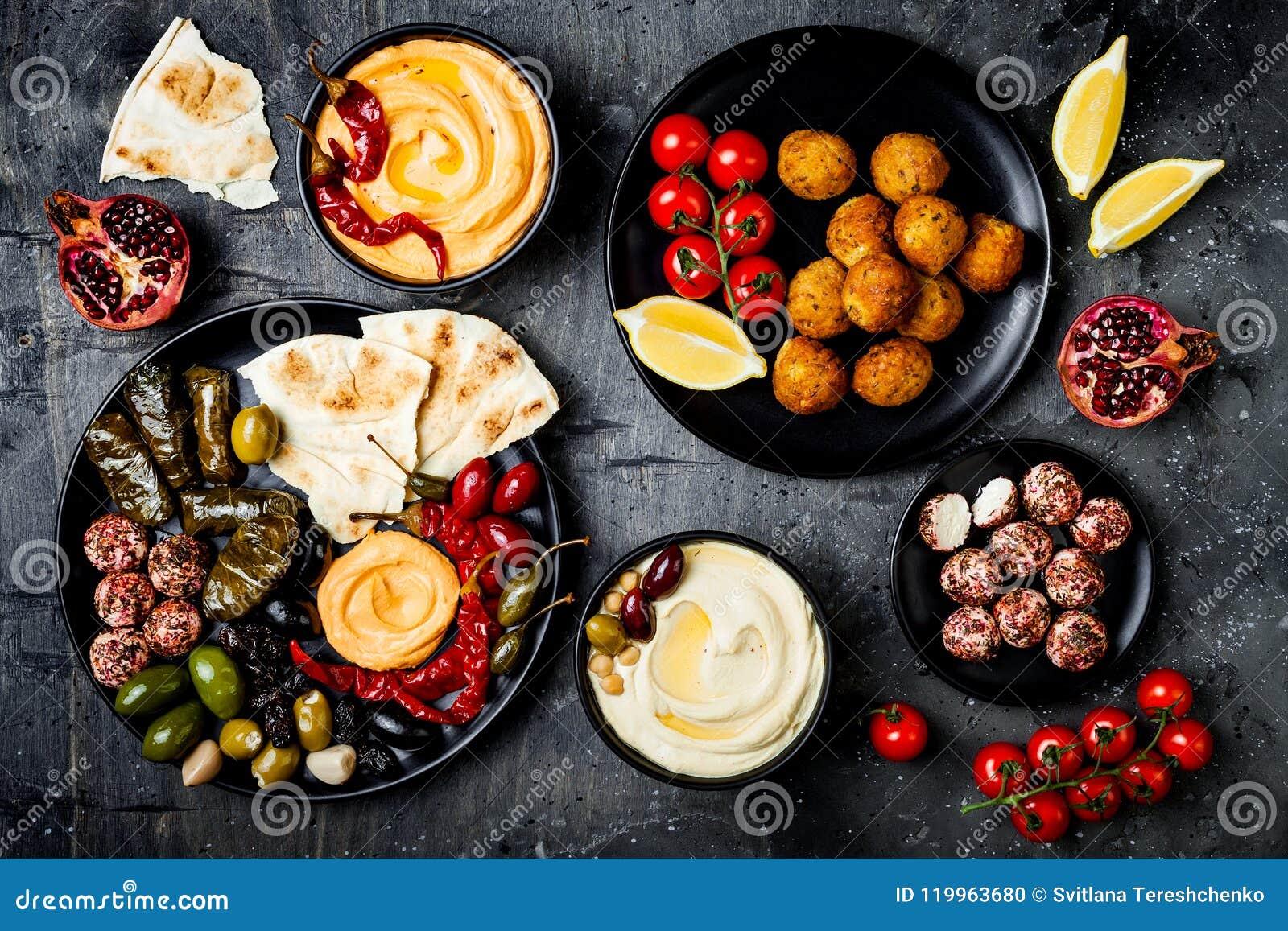 Culinária tradicional árabe A bandeja do Oriente Médio do meze com pão árabe, azeitonas, hummus, encheu o dolma, bolas do queijo