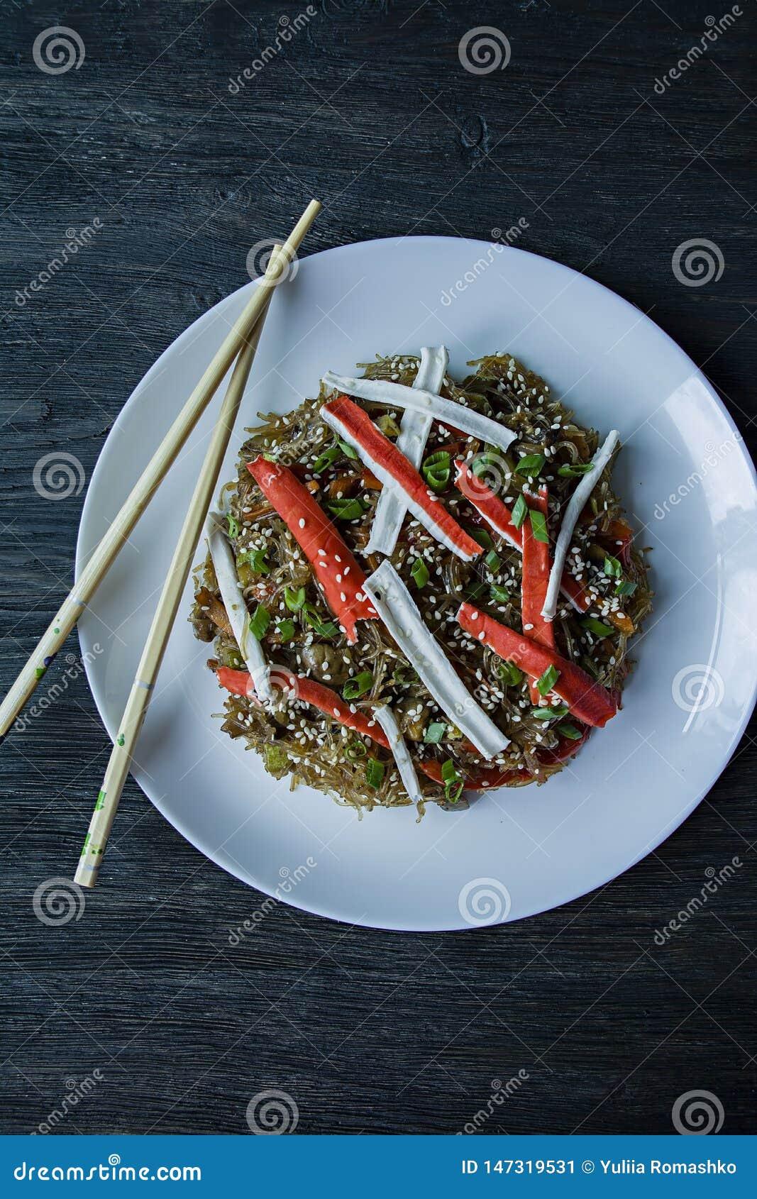 Culin?ria asi?tica Salada de Fenchoza fritada com os vegetais, decorados com verdes e varas do caranguejo Nutri??o apropriada Ali