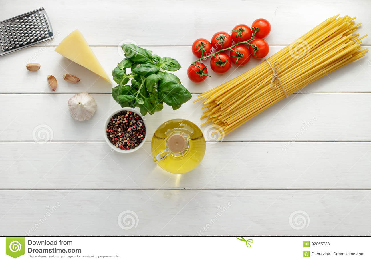 Culinary background with raw ingredients for pasta recipe on white wooden background.