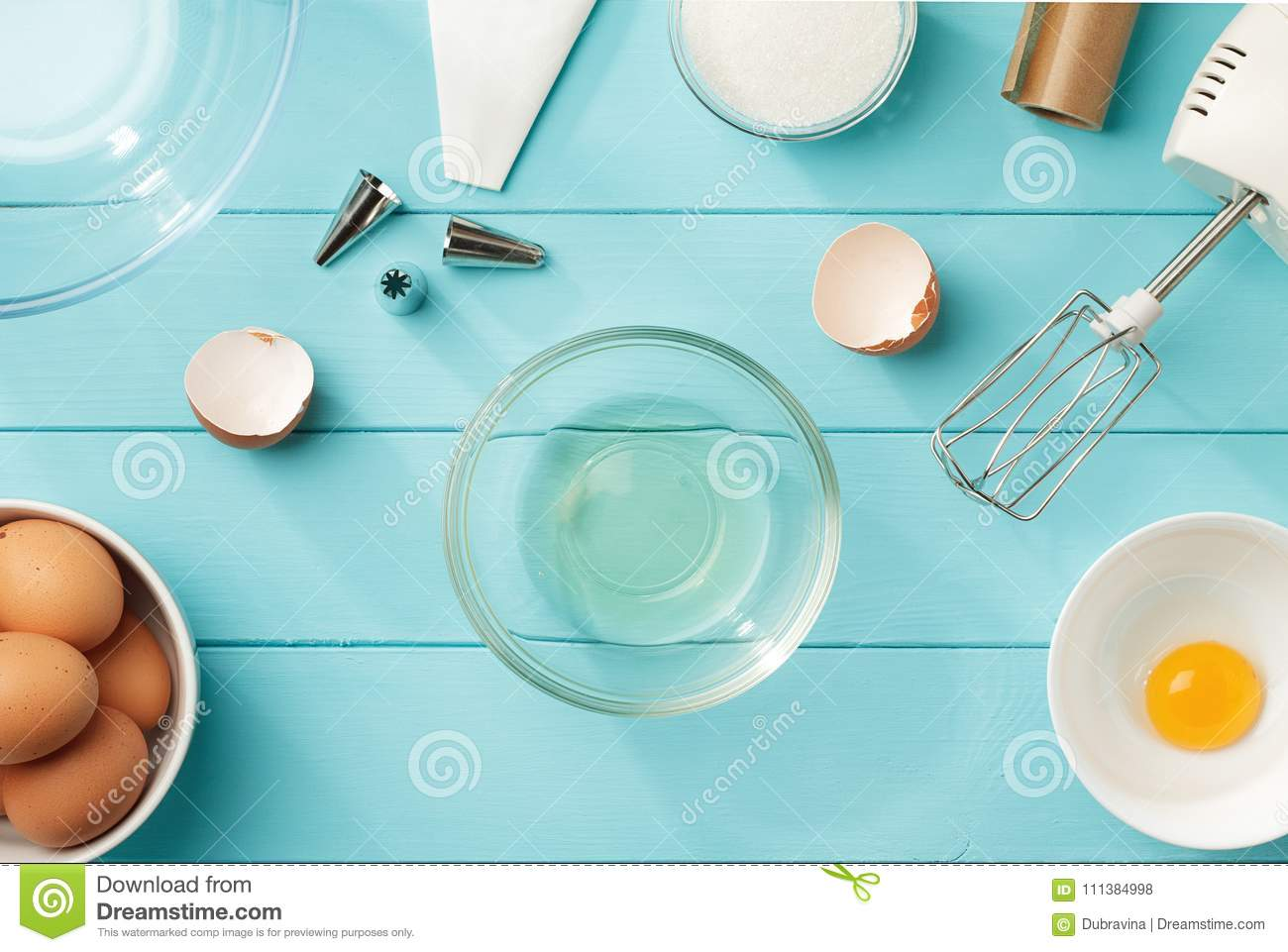 Culinary background with separated egg whites and yolks in the bowls on blue wooden table.