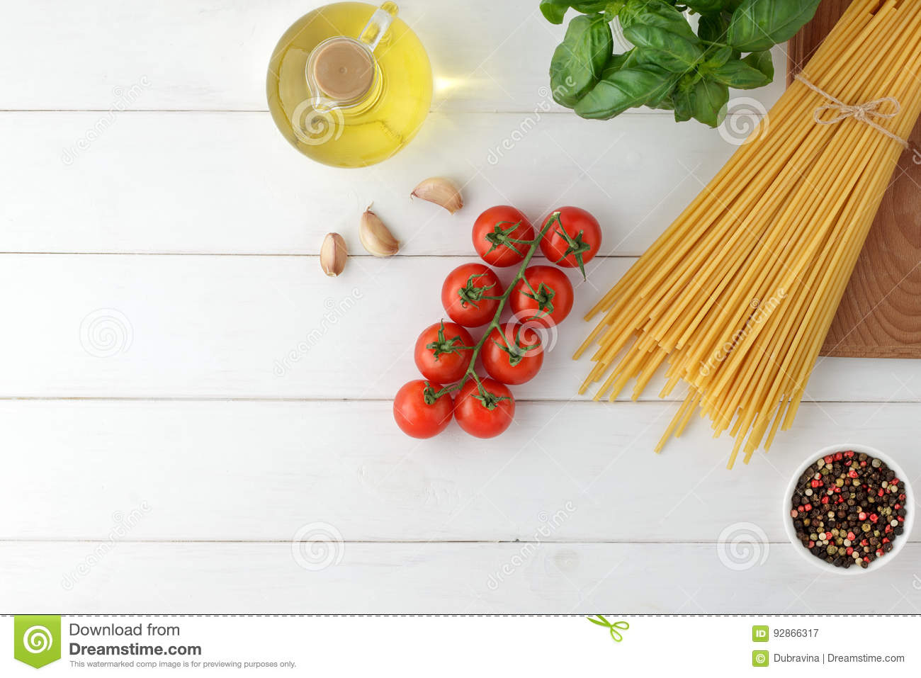 Culinary pasta background with dry bucatini, fresh basil and tomatoes on white wooden table.
