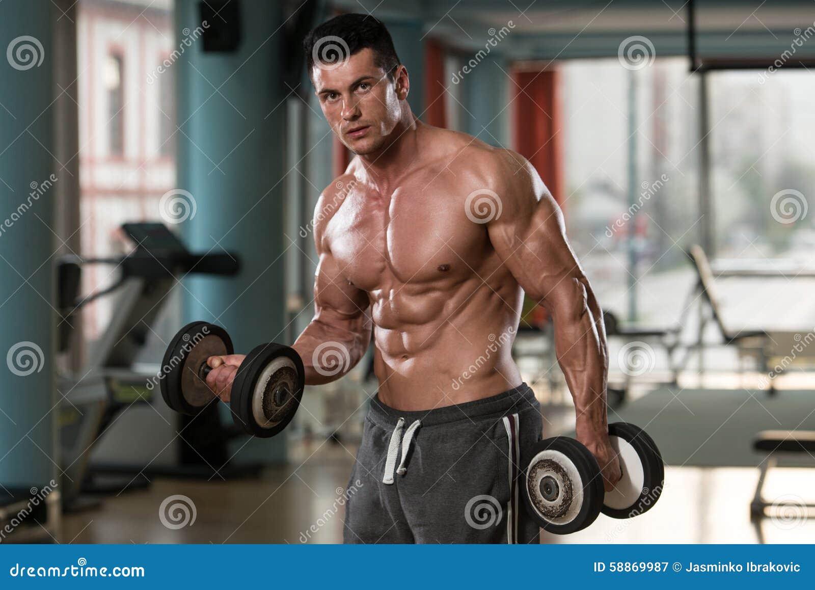 Culturista joven que ejercita el bíceps con pesas de gimnasia