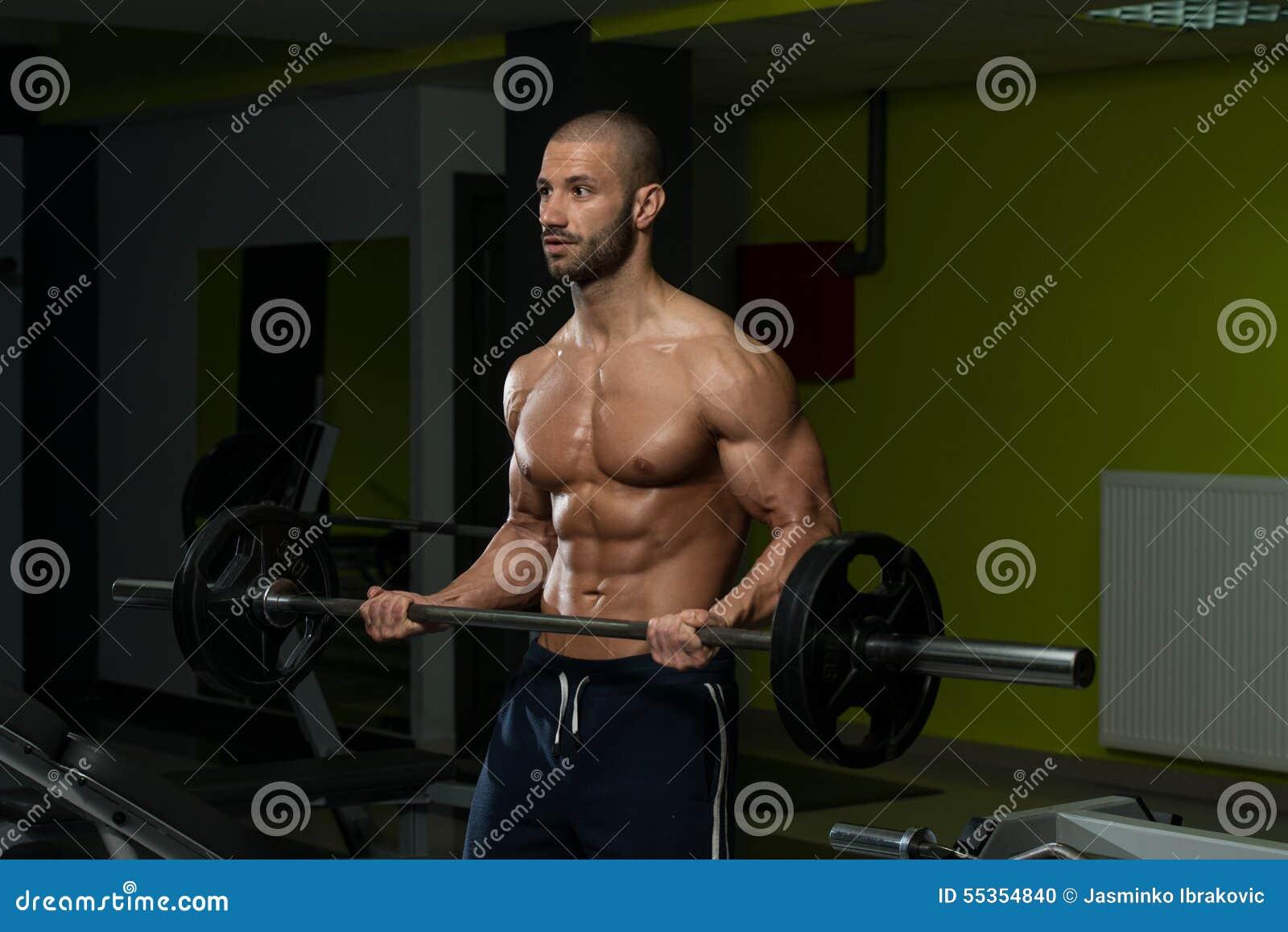 Culturista maschio che fa esercizio pesante per il bicipite