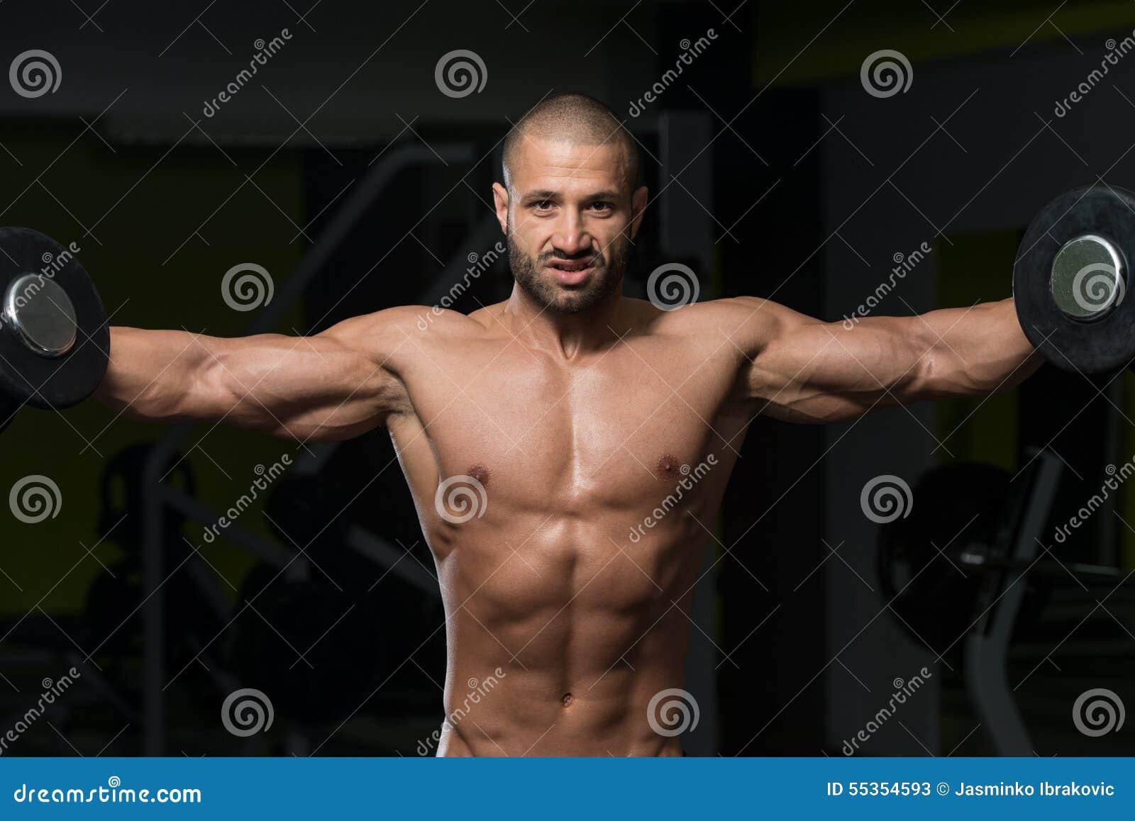 Culturista maschio che fa esercizio pesante per le spalle
