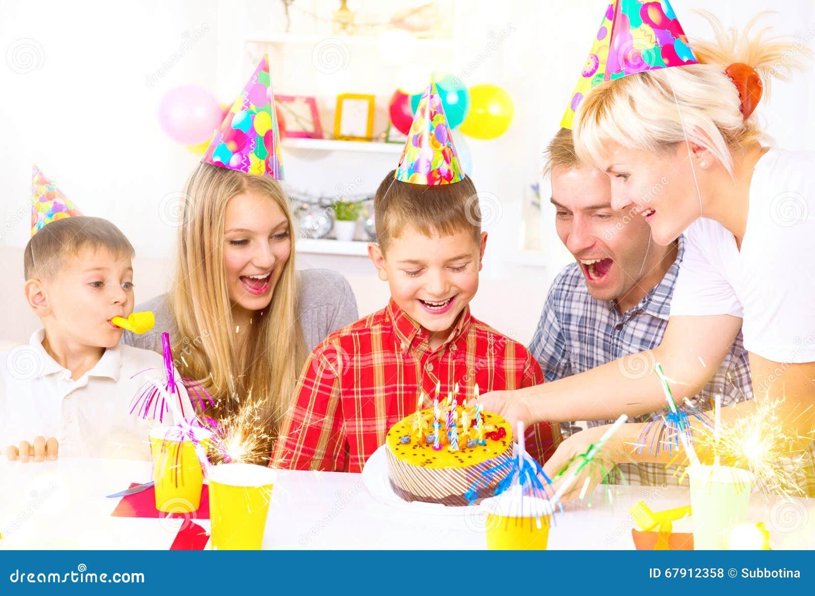 Cumpleaños El niño pequeño sopla hacia fuera velas en la torta de cumpleaños