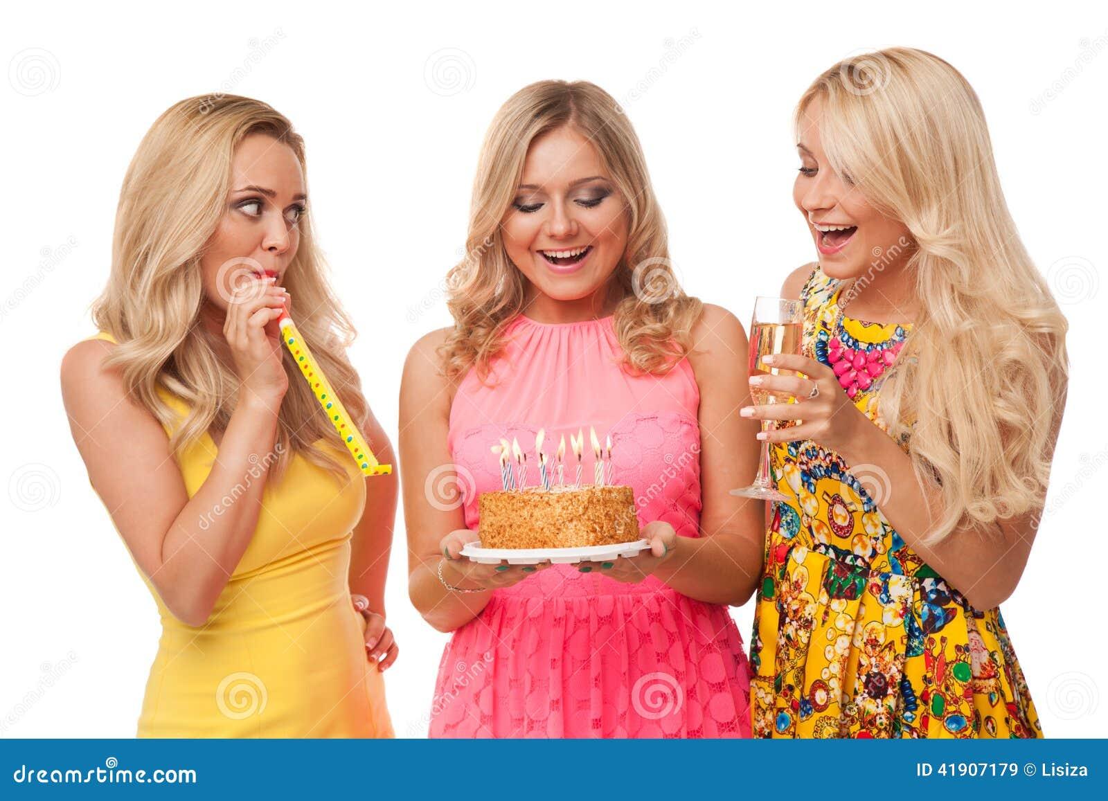 Cumpleaños rubio de la celebración de tres muchachas con la torta y el champán