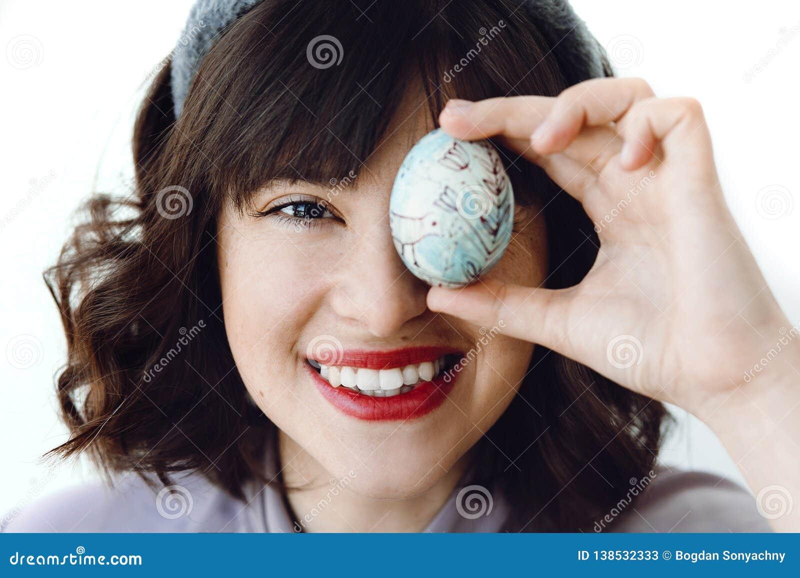 Cumprimentos felizes da Páscoa Jovem mulher bonita nas orelhas do coelho que sorri e que guarda o ovo da páscoa perto da cara no