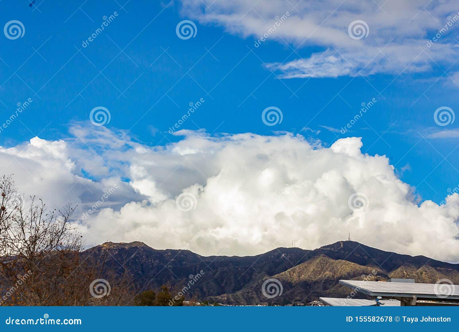 Cumulos, nimbus, nuvole con le montagne della cresta di Angeles, cielo blu, luce solare, pannelli solari