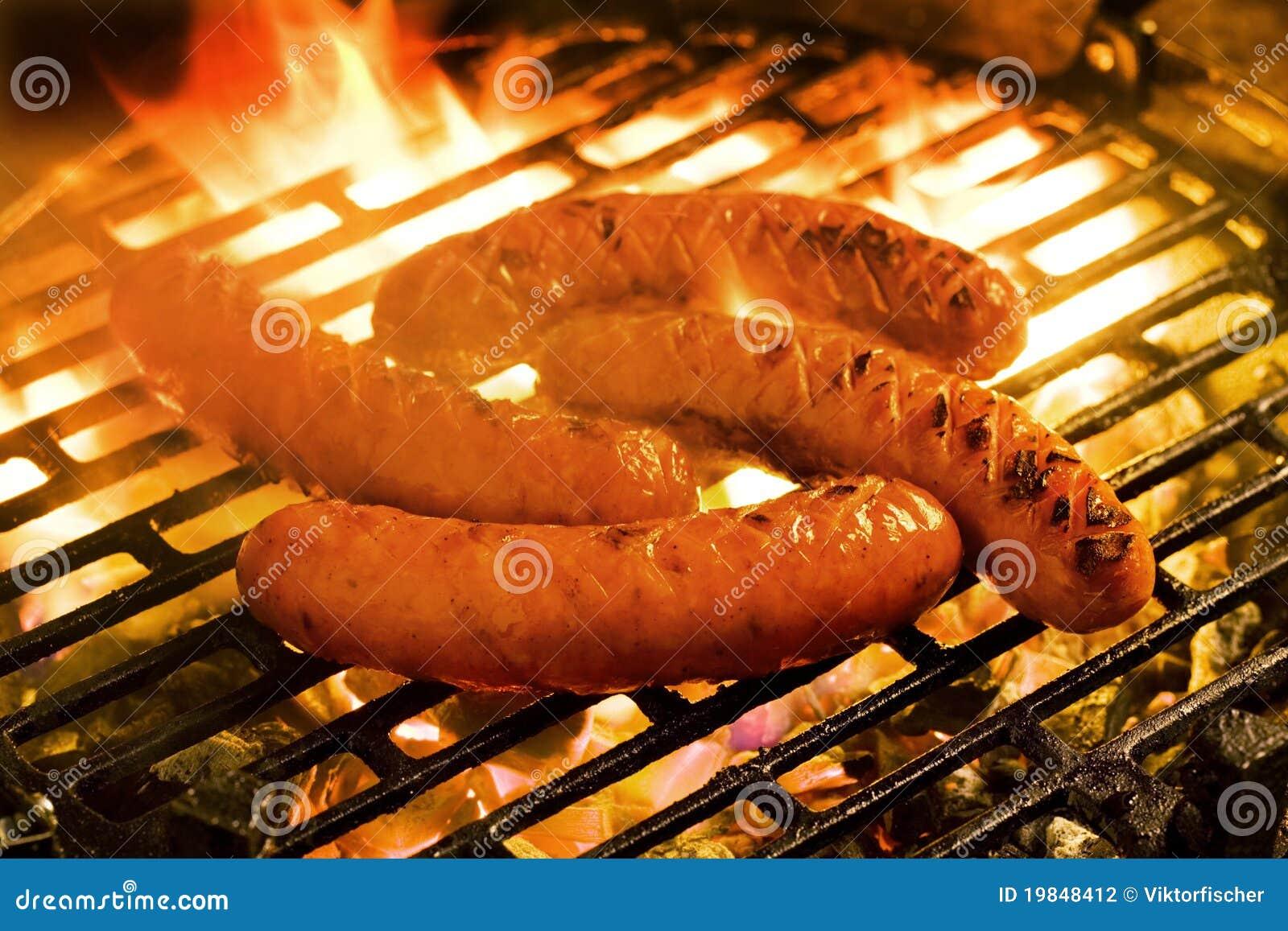 Cuocere le salsiccie alla griglia su una griglia del carbone di legna