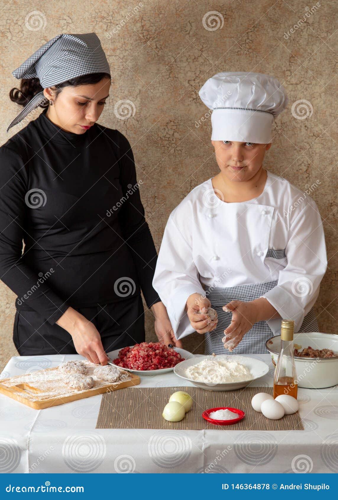 Cuoco del ragazzo e cuoco della madre nella cucina