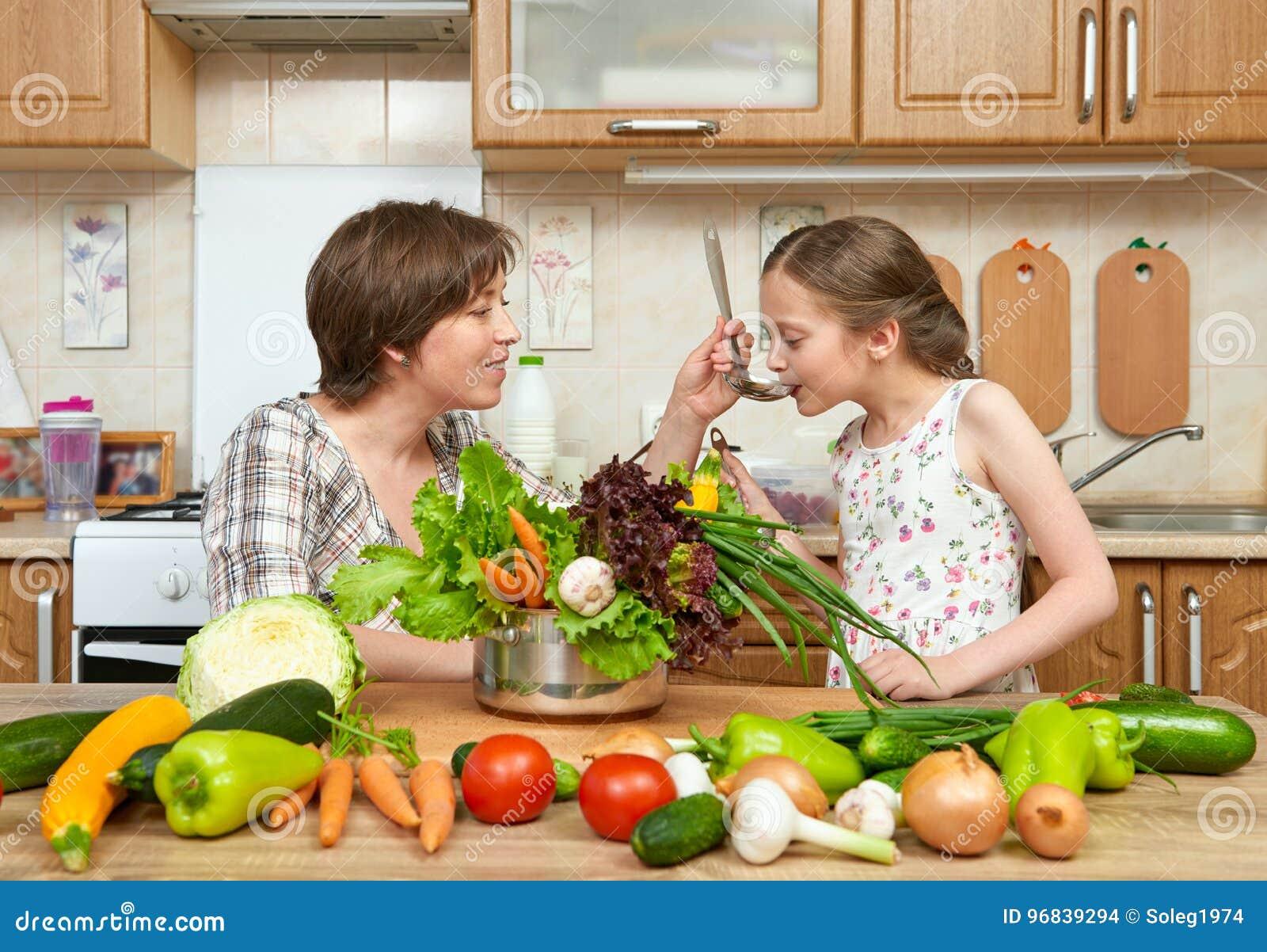 Cuoco della figlia e della madre e minestra di gusto dalle verdure Interno domestico della cucina Genitore e bambino, donna e rag