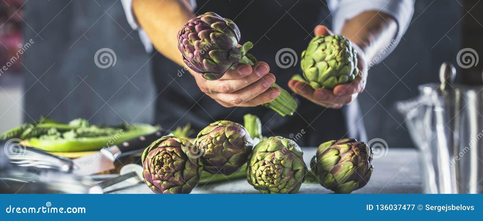 Cuoco unico che taglia i carciofi per la preparazione della cena - uomo che cucina dentro la cucina del ristorante