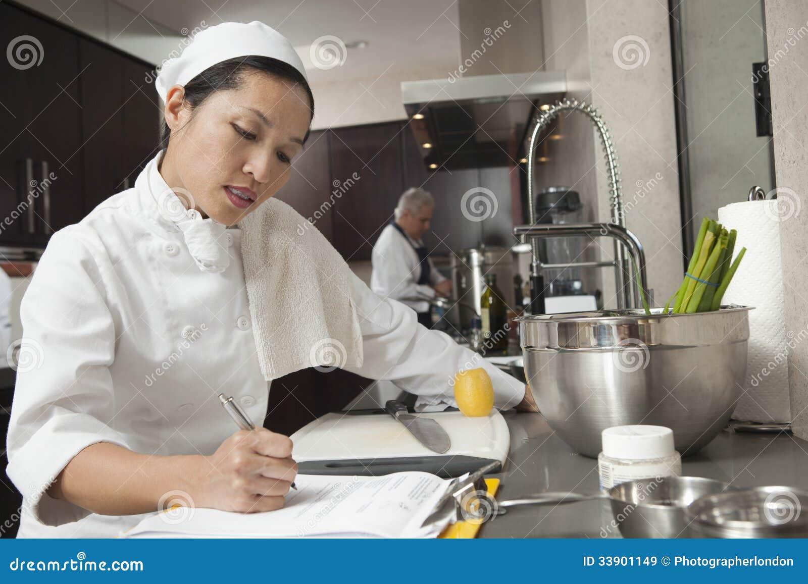 Cuoco unico femminile Writing On Clipboard in cucina