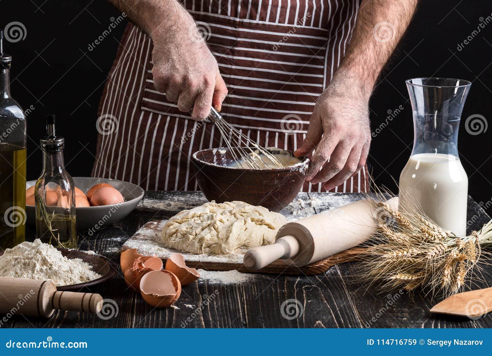 Cuoco unico maschio che monta le uova nel forno sulla tavola di legno Ingredienti per la cottura i prodotti o della pasta della f