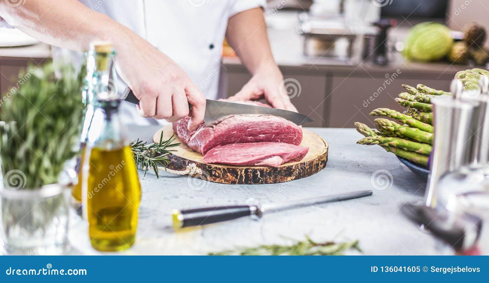 Cuoco unico nella cucina del ristorante che cucina, sta tagliando la carne o la bistecca