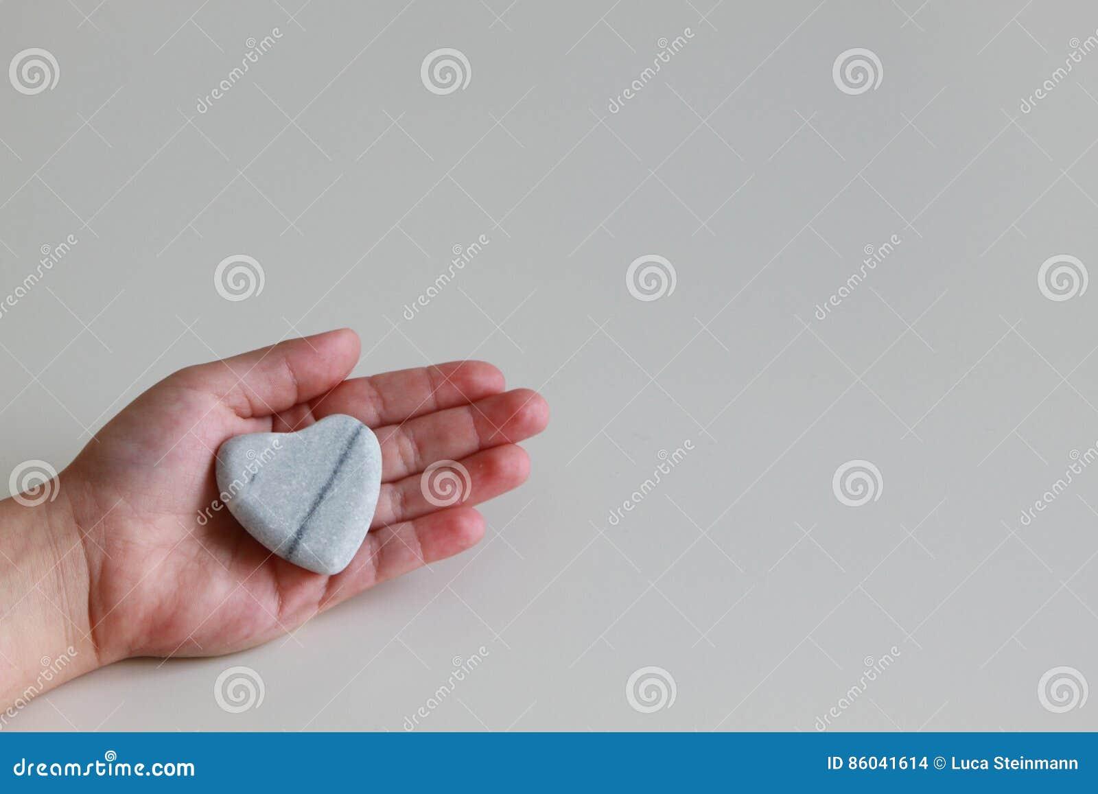 Cuore della tenuta del bambino piccolo della pietra a disposizione