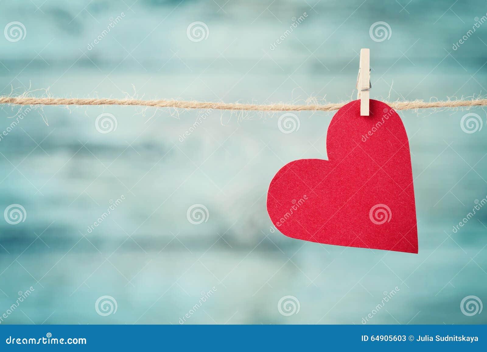 Cuore di carta che appende sulla corda contro il fondo di legno del turchese per il giorno di biglietti di S. Valentino