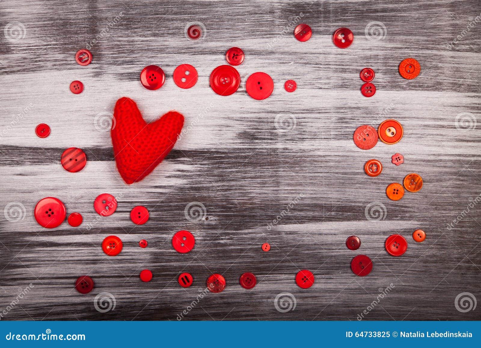 Cuore tricottato rosso e molti bottoni rossi