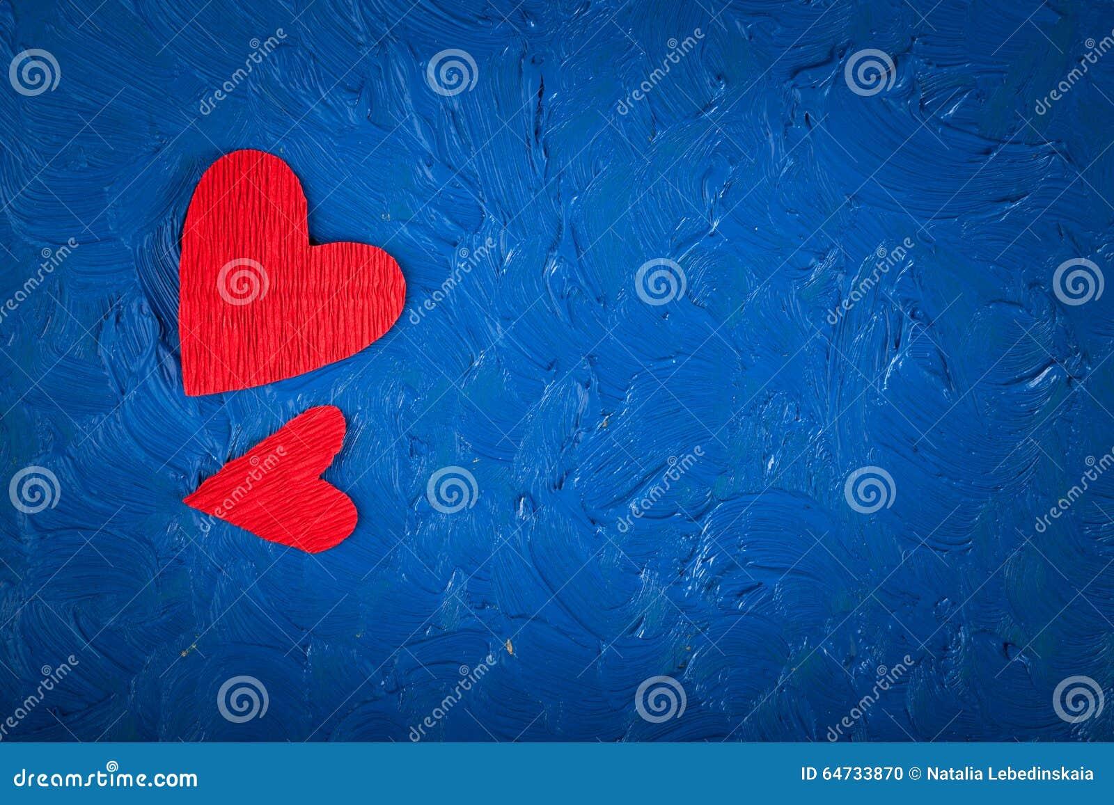 Cuori di carta rossi su un San Valentino blu del fondo