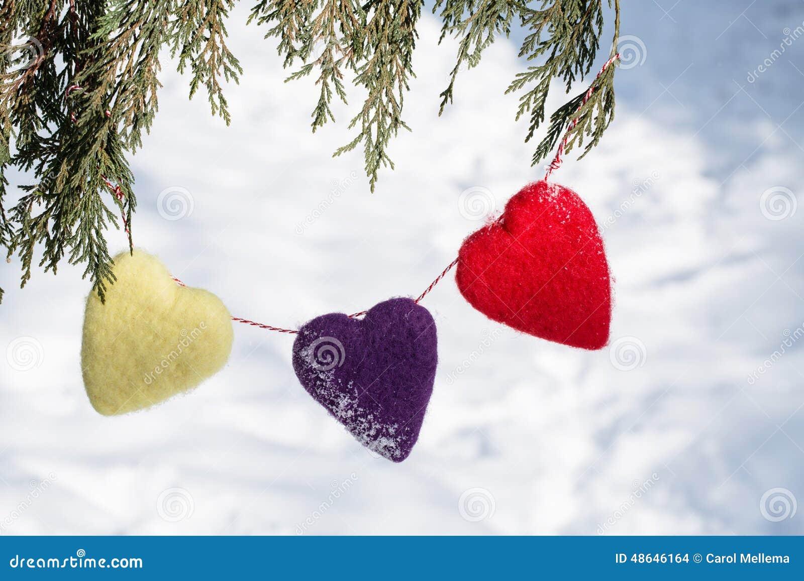 Cuori di giorno di biglietti di S. Valentino che pendono dal pino
