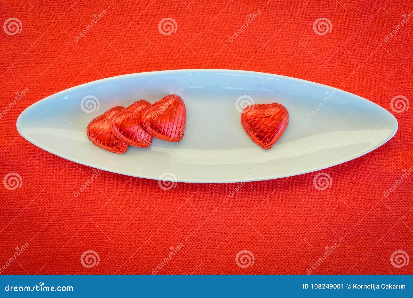 Cuori rossi del cioccolato su un piatto ceramico Giorno del `s del biglietto di S