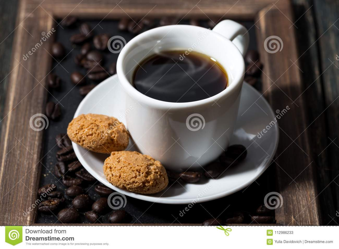 Cup of black coffee and cookies on a tray, closeup