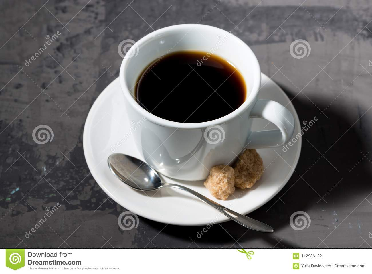Cup of black coffee on a dark background, top view