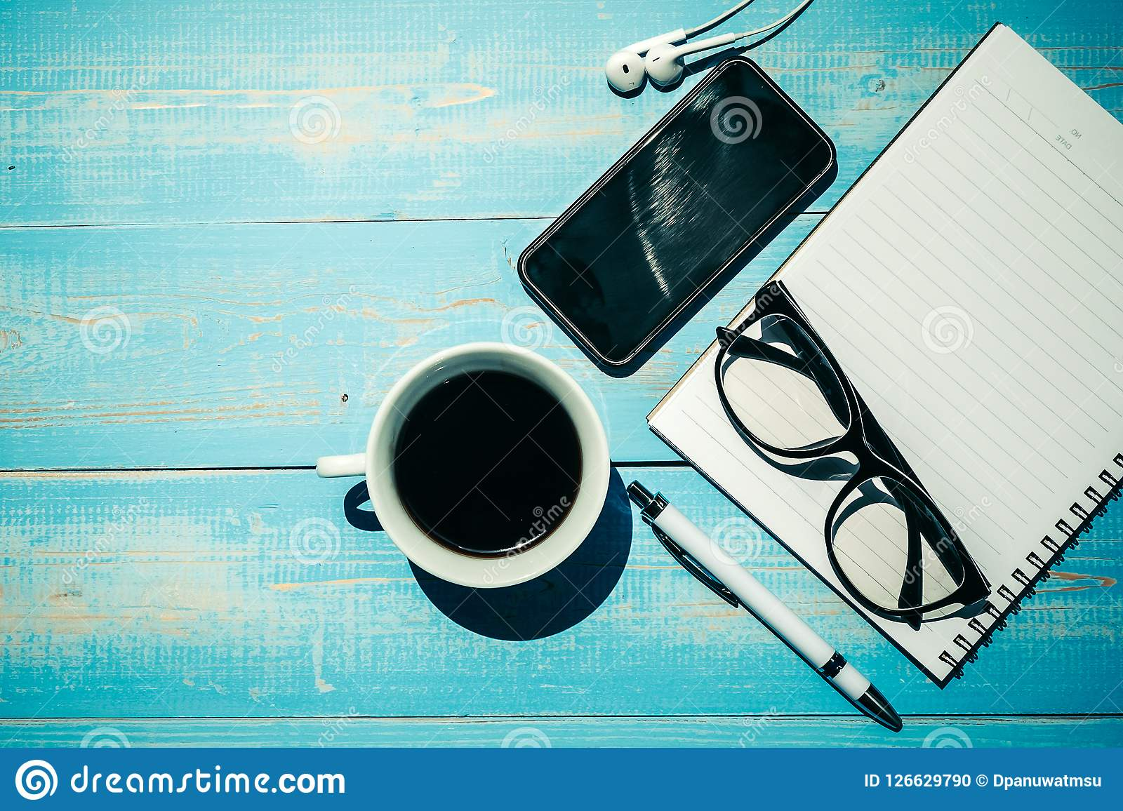 Cup of black coffee and smart phone with office supplies; pen, notebook and eyes glasses on wooden table background