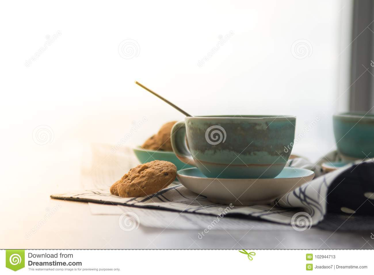 Cup of black coffee with spoon on supported dish on fabric on bl
