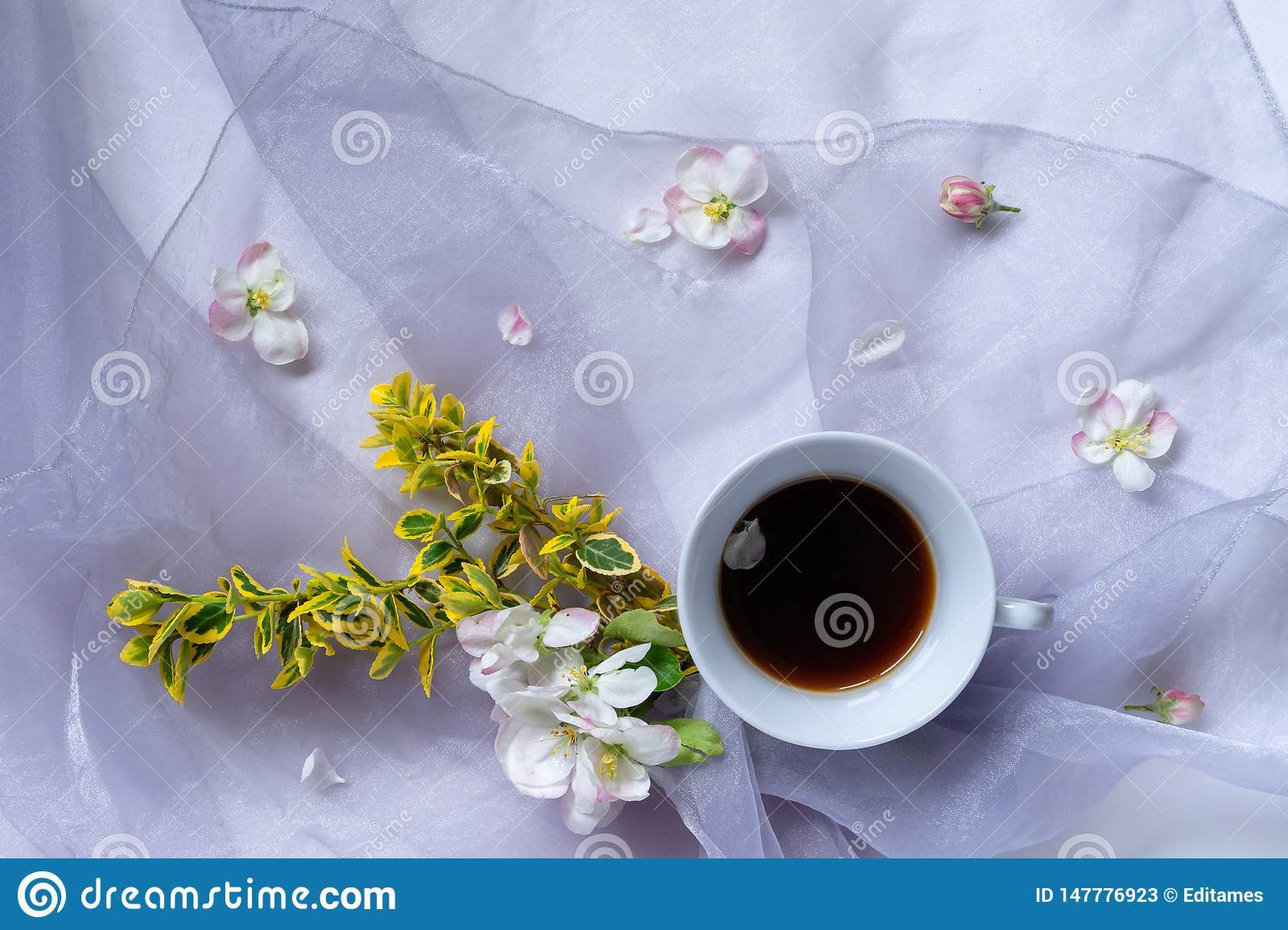 A cup of black coffee on tehe table with bouquet