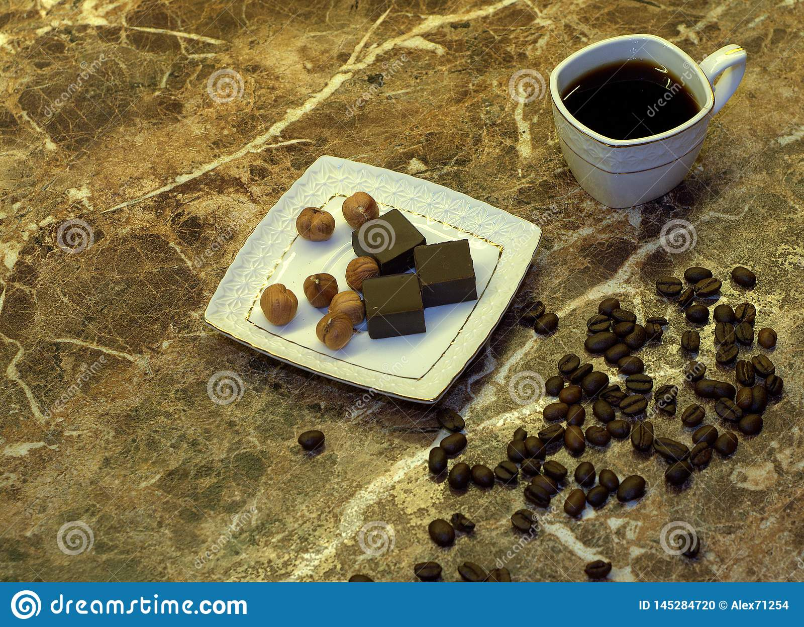A cup of black coffee in a white porcelain cup, chocolates on a saucer and coffee beans are on a table made of beige marble. Close