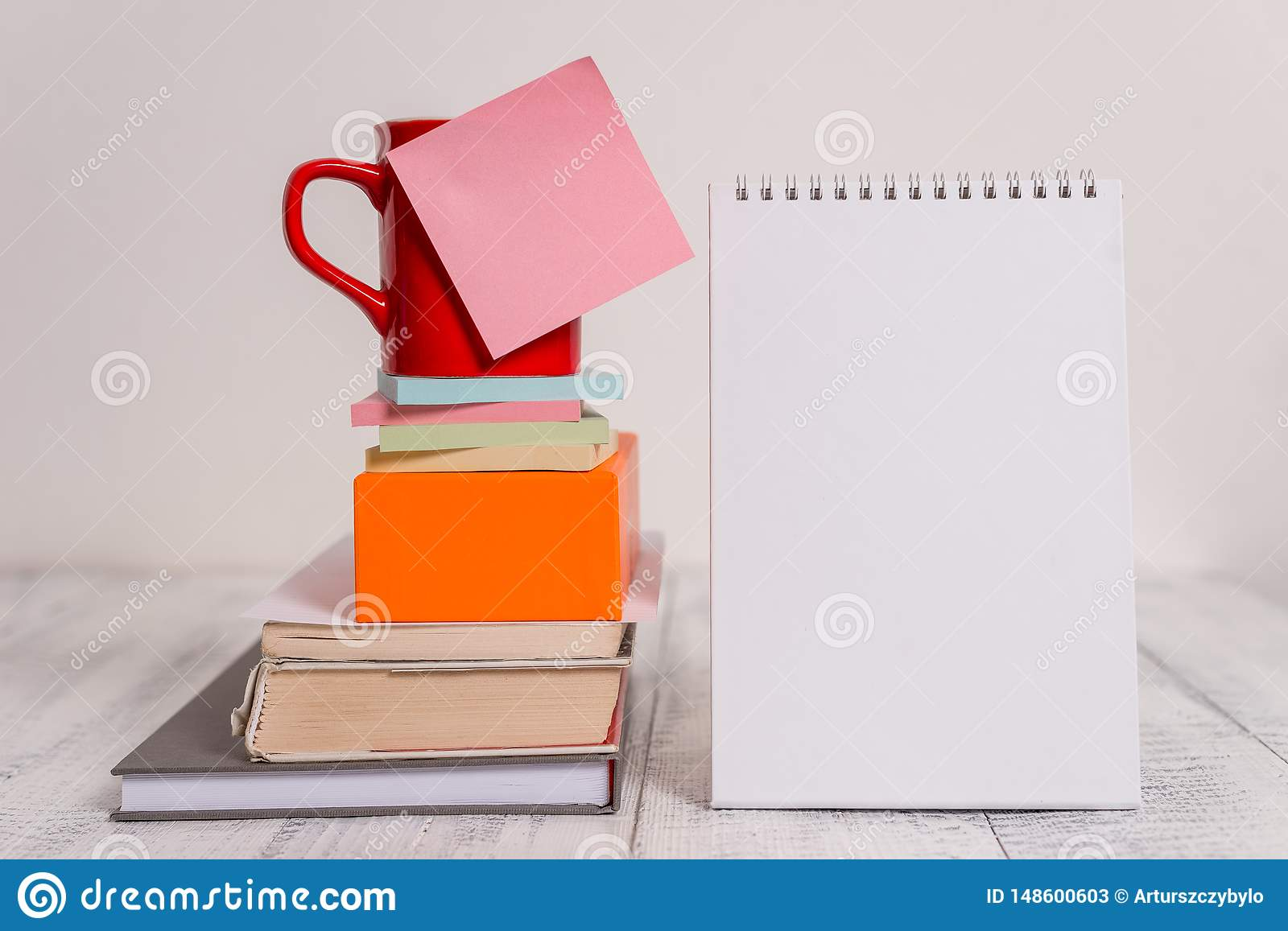 Cup blank colored sticky note stacked note pads books square box spiral lying retro vintage rustic old table background