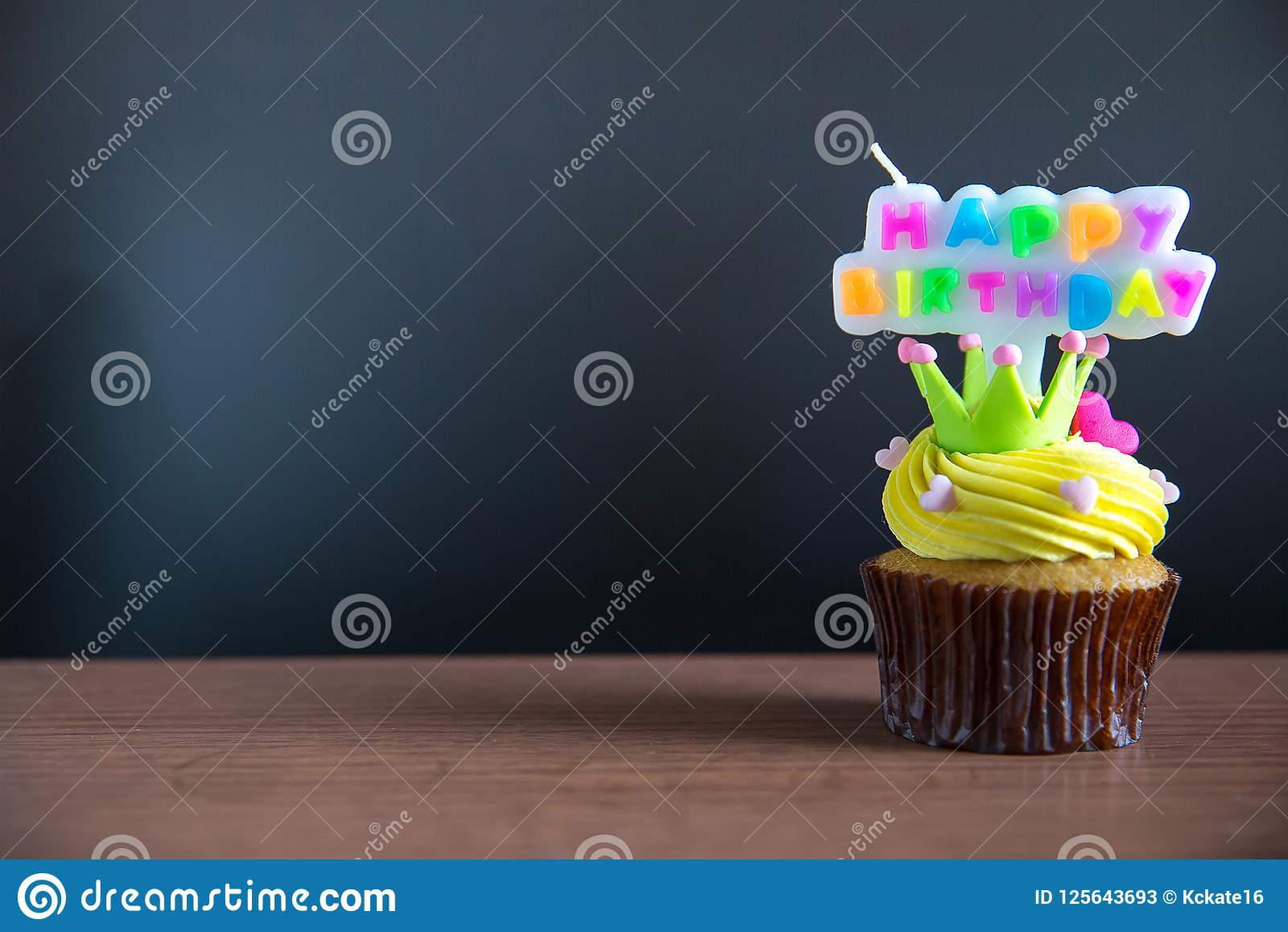 Cup cake and happy birthday text candle on cupcake ..Birthday cupcake with a happy brithday text candle.