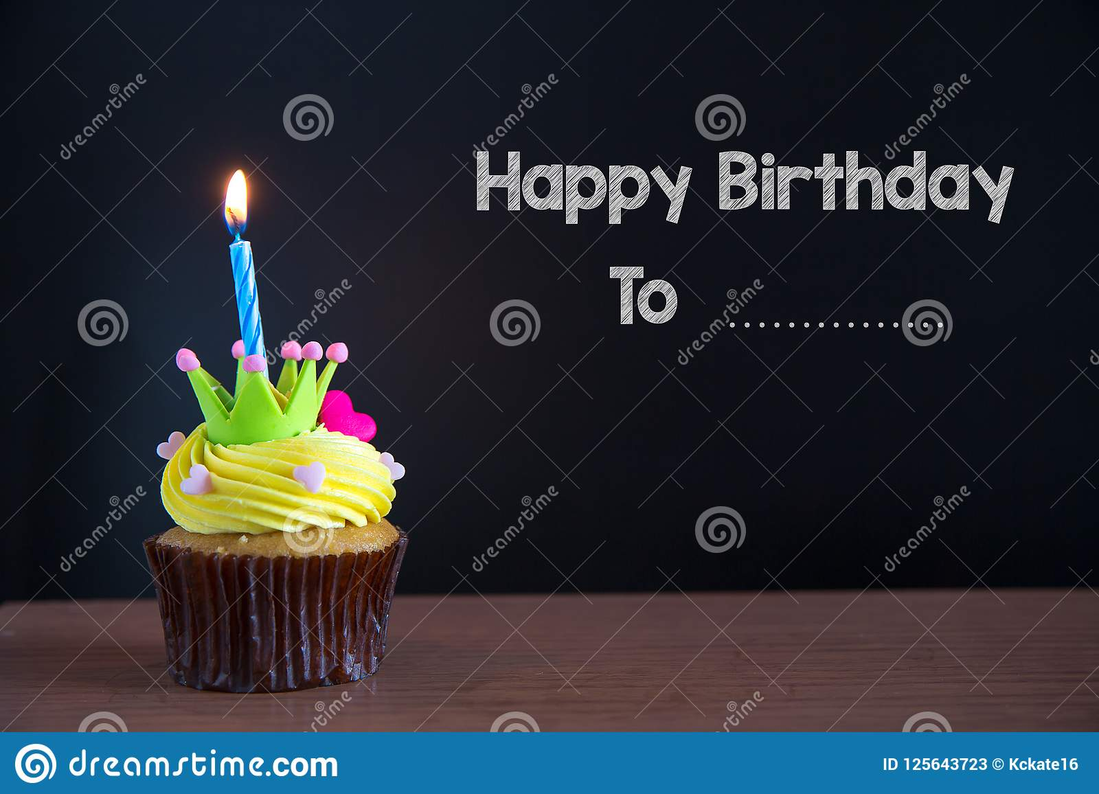 Cup cake and happy birthday to you text on chalkboard background..