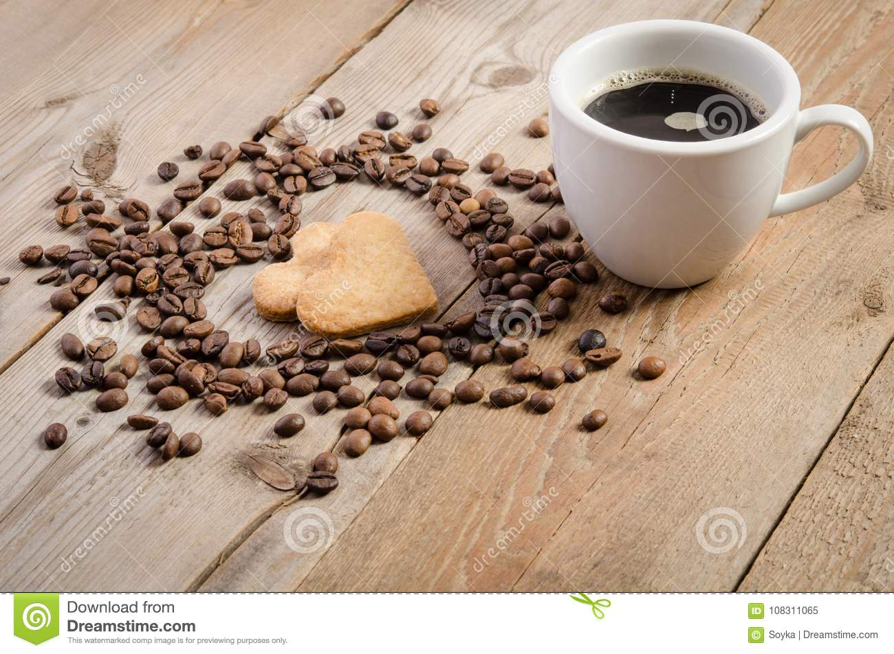 Cup of coffe and Frame-heart from coffee beans and two cookies-heart