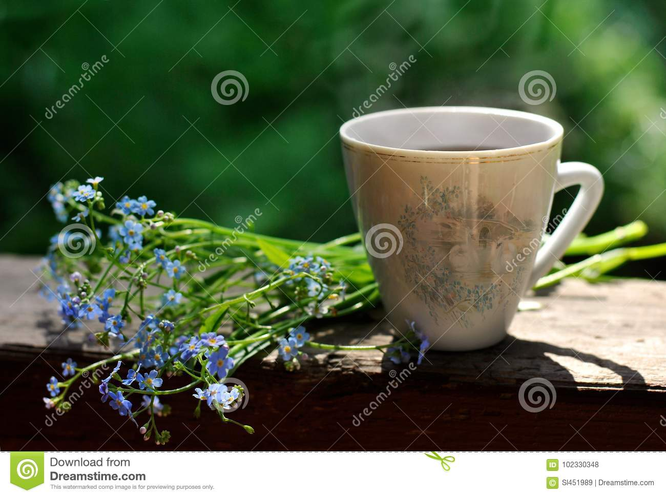A Cup Of Coffee And Blue Flowers Near It On A Green Garden
