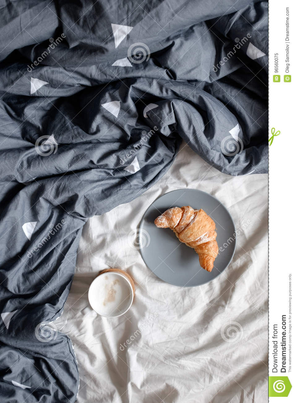 A cup of coffee and a croissant on a plate on a cozy bed