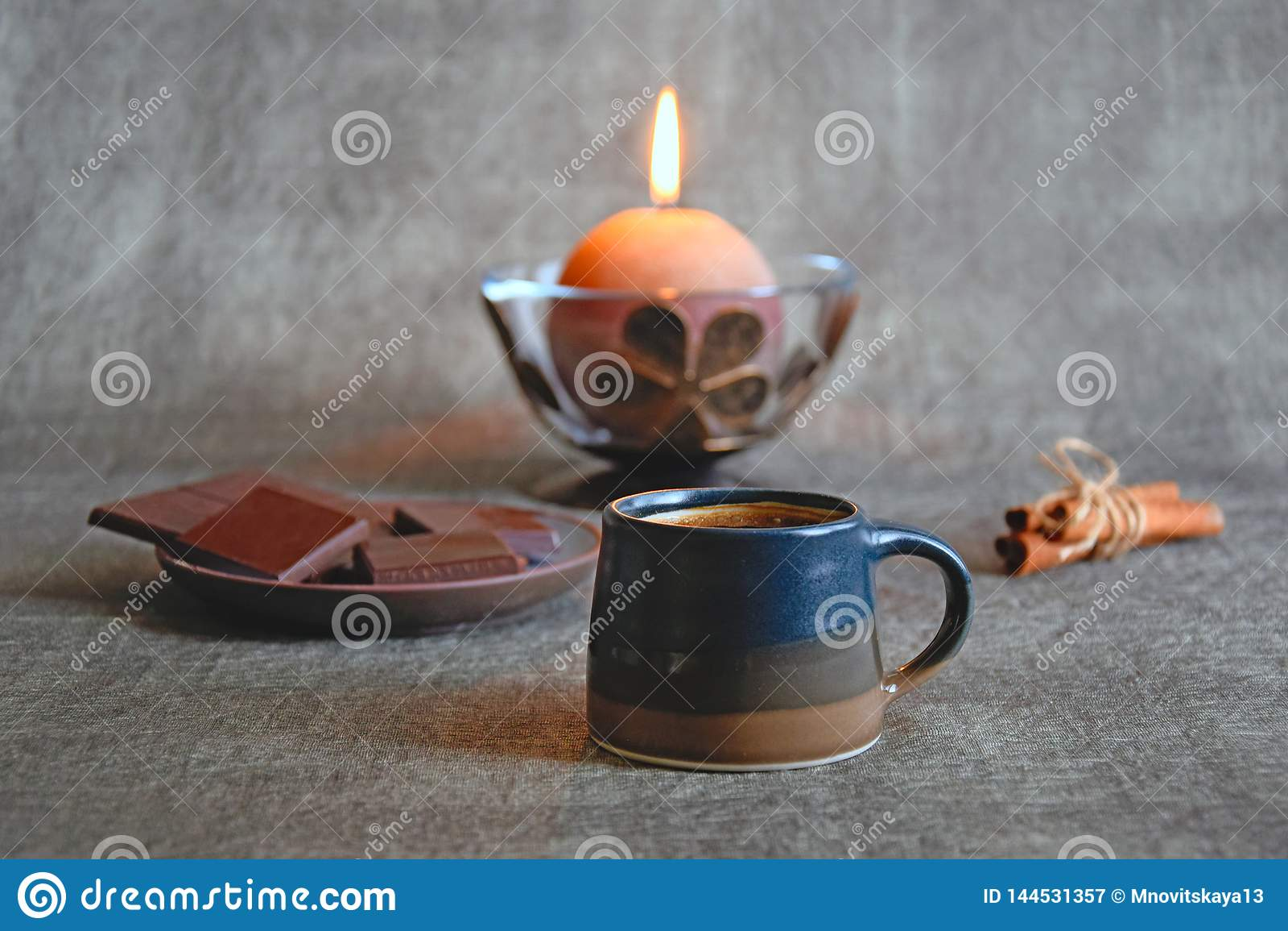 Cup of coffee, dark chocolate, cinnamon sticks and burning decorative candle
