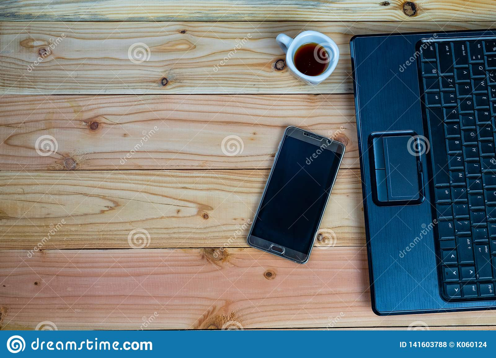 a cup of coffee with labtop and a pen with book on wood desk