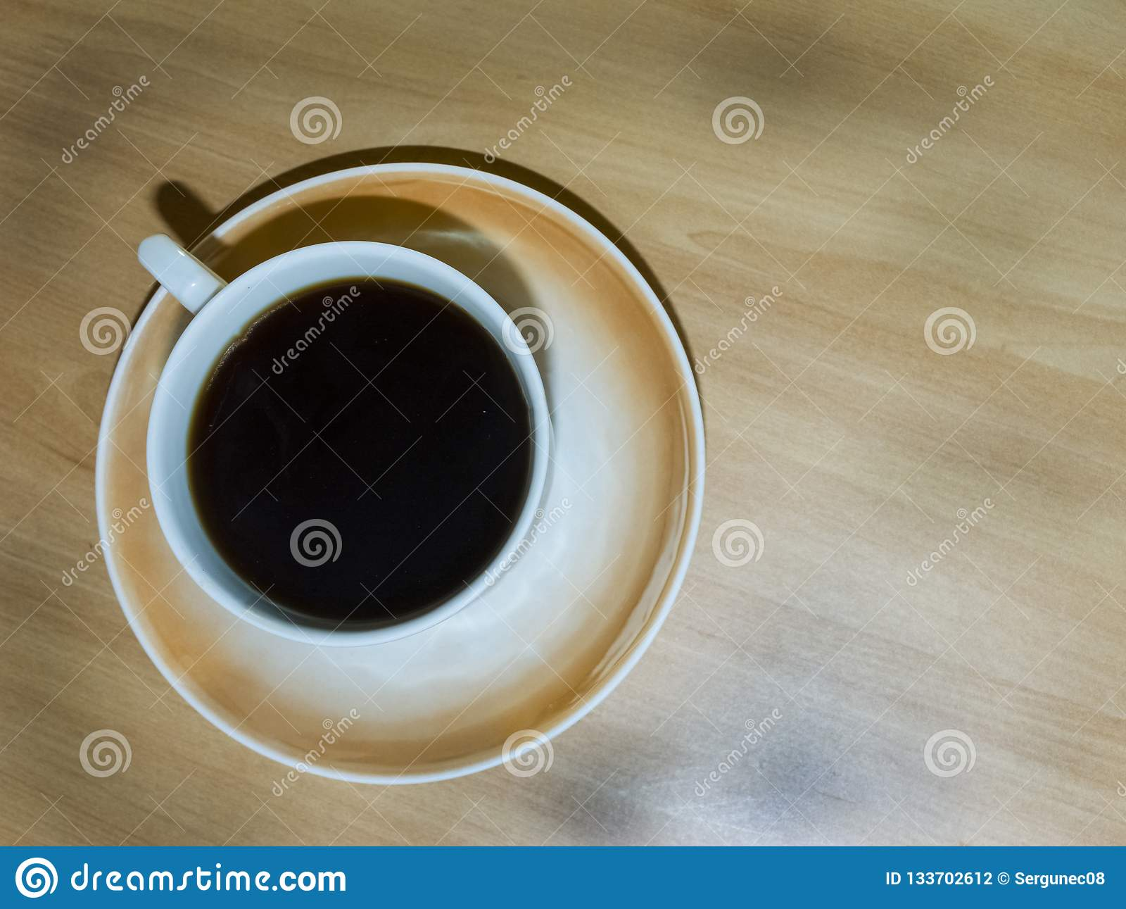 A Cup of coffee on a light wooden table.