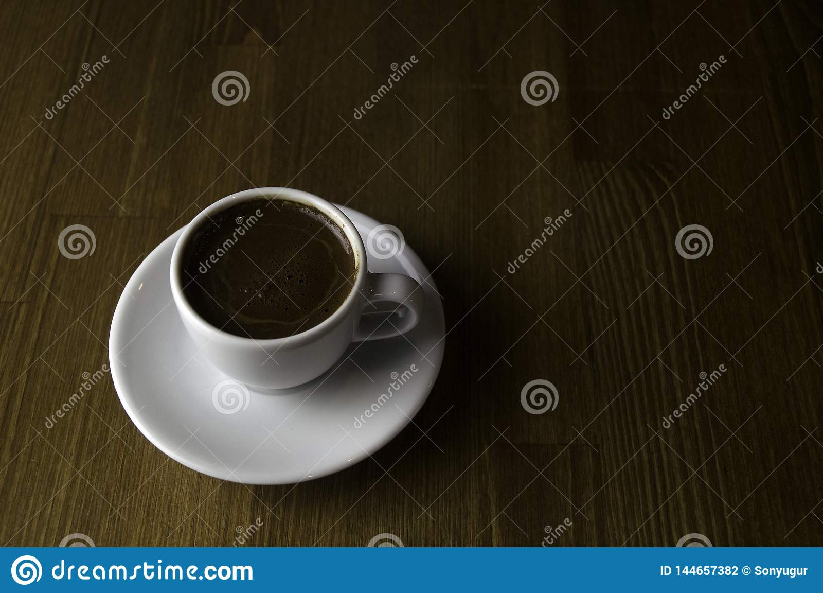 a cup of coffee with milk and brown table