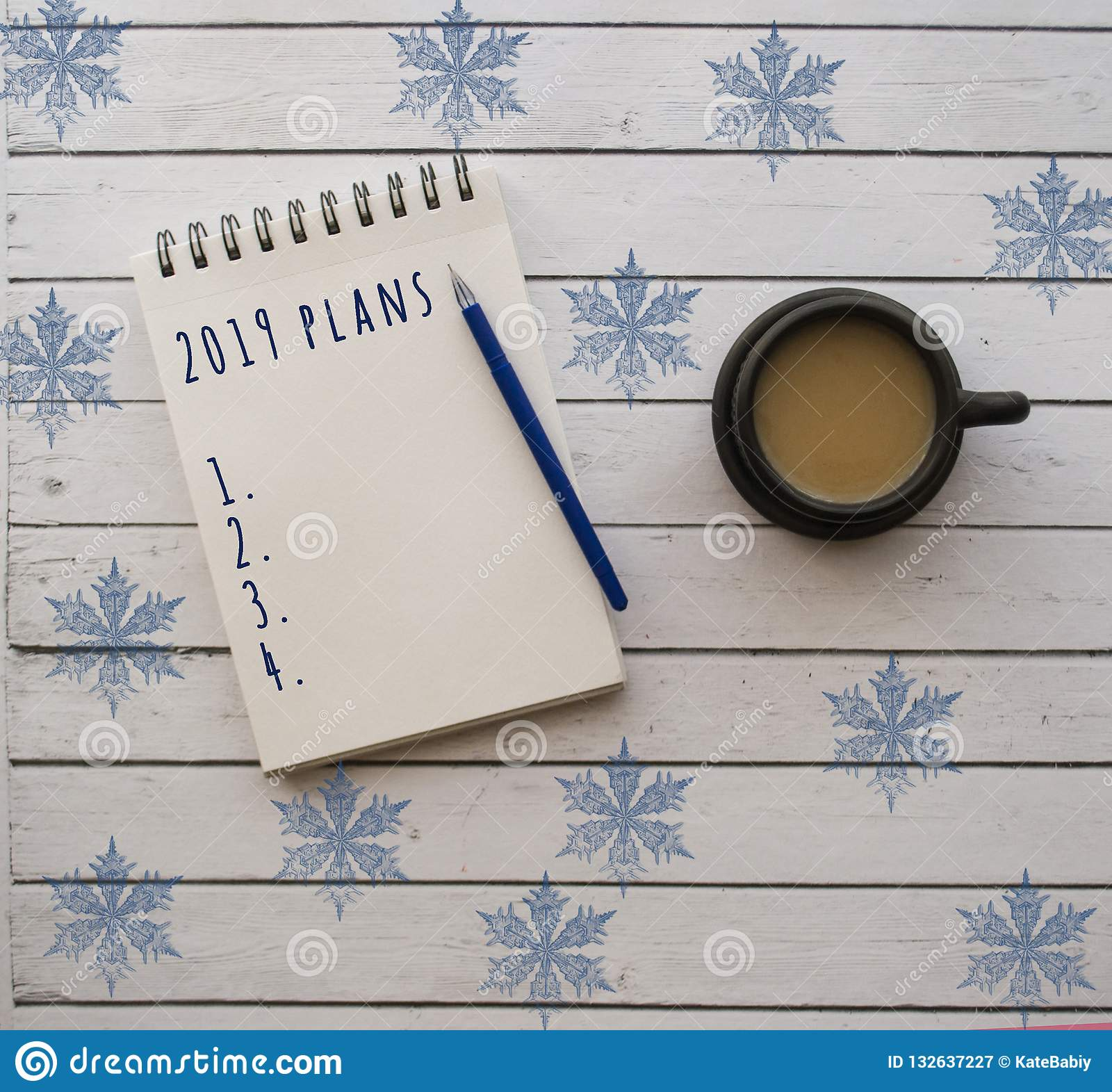 A cup of coffee and notepad on white wooden table.