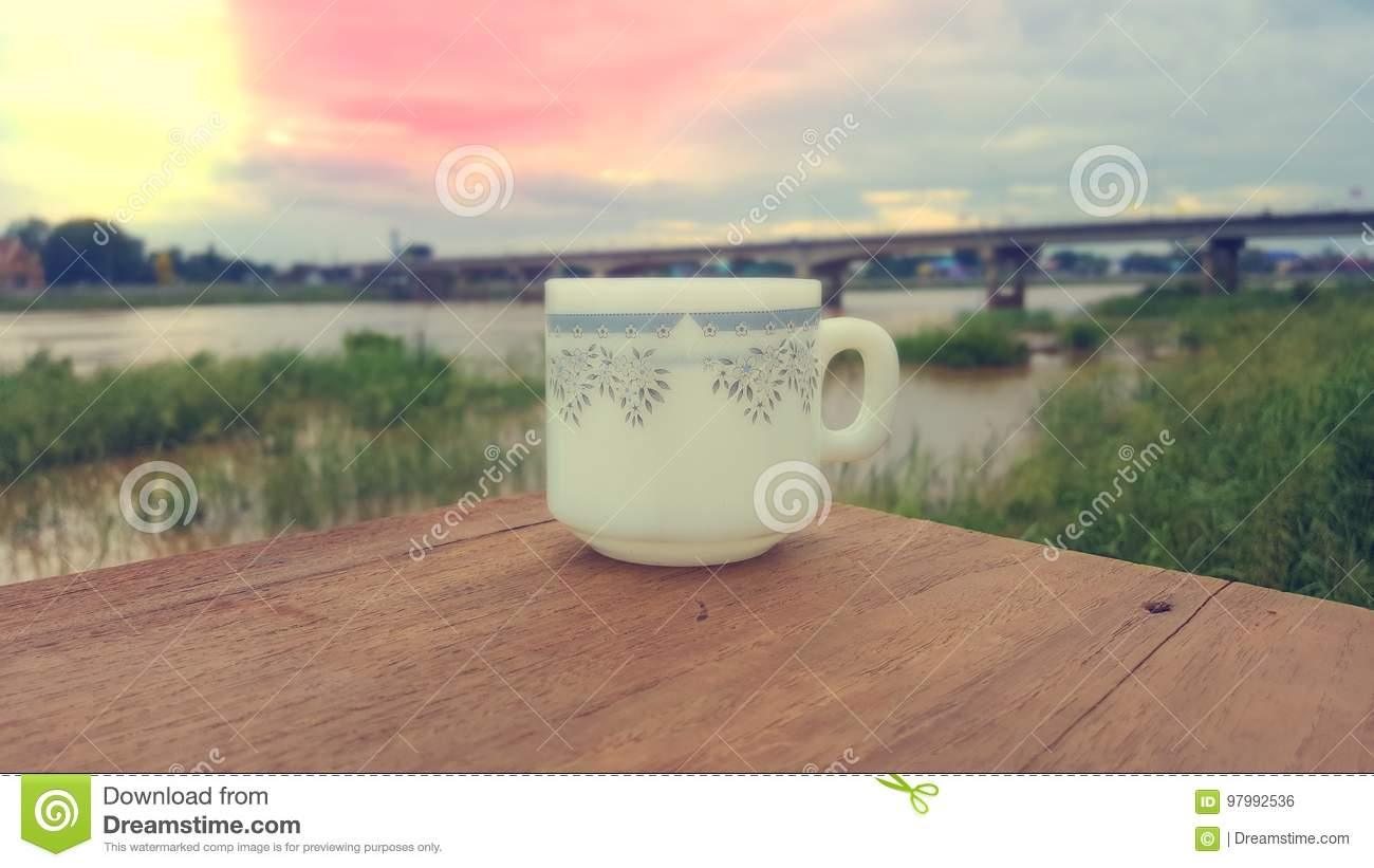 A cup of coffee is placed on a wooden floor in the morning