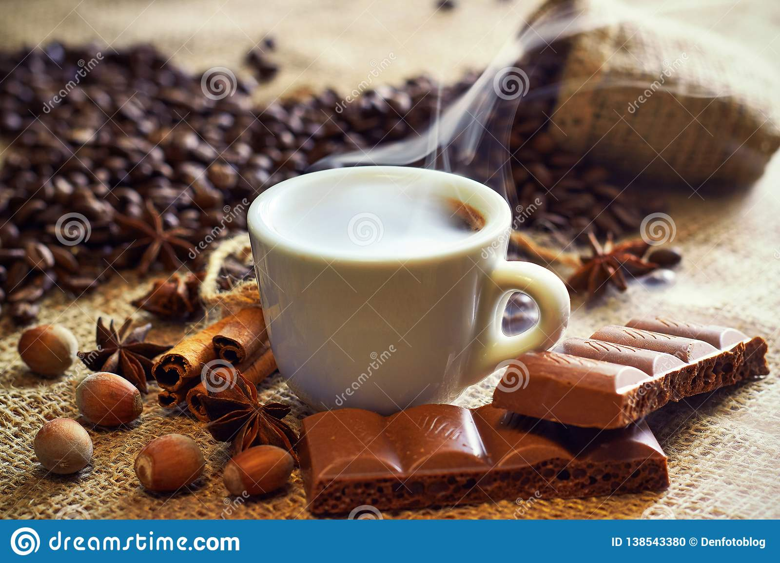 A cup of coffee on a plate with cinnamon and anise and chocolate, grains of coffee on sackcloth