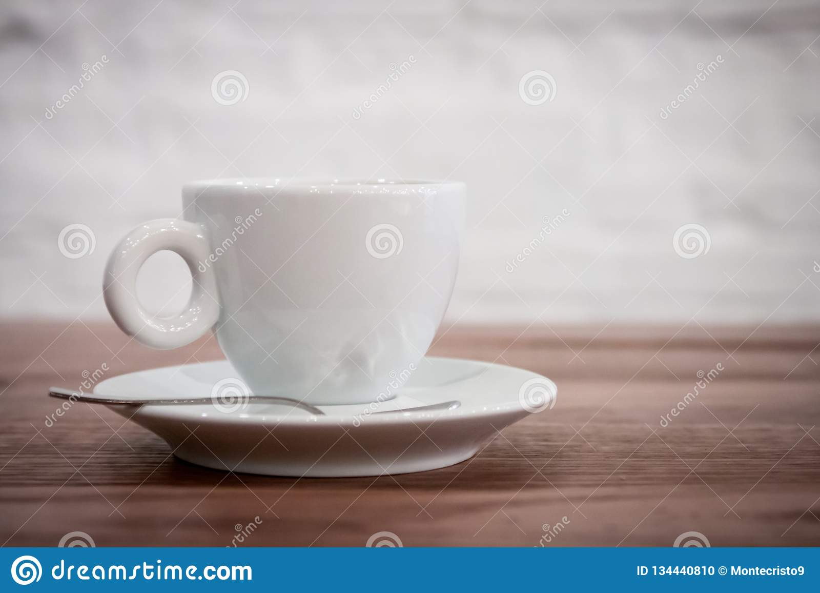 A Cup Of Coffee On A Saucer And A Spoon Stands On A Wooden Table